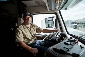 Truck driver (30s) sitting in cab of semi-truck.